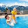 Coffre de rangement an argent sur une terrasse avec piscine et balustrade en verre. Une mère jouant avec son enfant