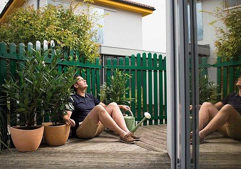 [Translate to Fransösich:] Mann sitzt nach getaner Arbeit vor einem grünen Lattenzaun aus Aluminium und schaut zufrieden in die Ferne