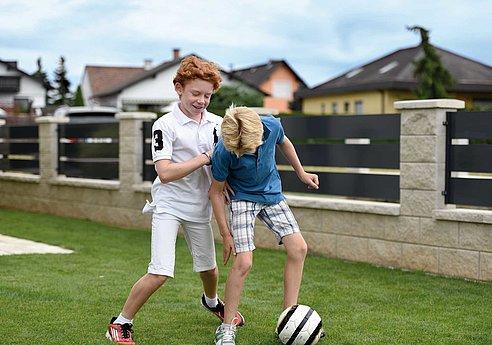 [Translate to Fransösich:] Zwei Buben spielen Fußball vor einem Aluminiumzaun mit breiten Querlatten in anthrazit