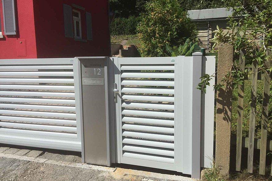 Portillon de jardin et clôture de jardin couleur blanche avec lamelles devant une maison rouge