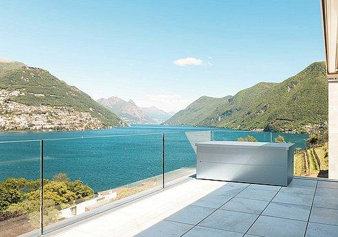 Coffre de rangement en argent sur une terrasse moderne au bord de la mer avec balustrade en verre