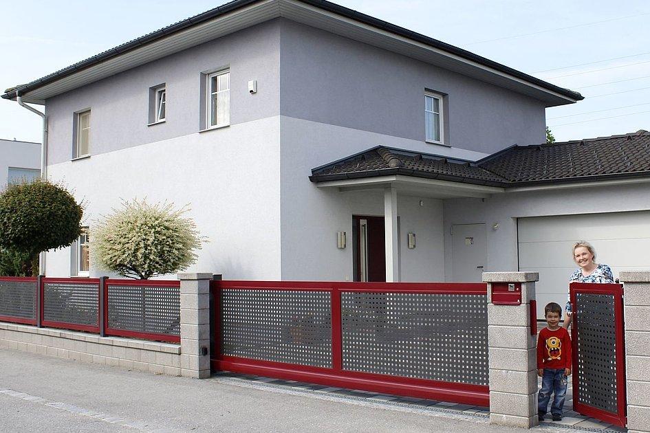 Portail coulissant multicolore en tôle perforée devant une maison unifamiliale dans un domaine