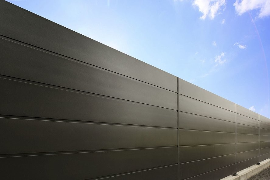 Vue rapprochée d'une clôture occultante moderne avec des lattes pleines noires en aluminium
