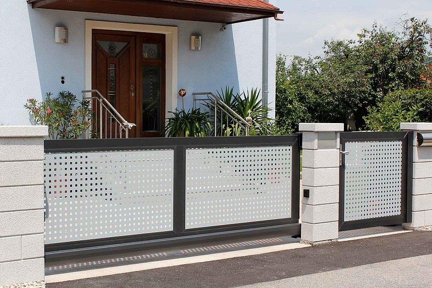 portail coulissant électrique et portillon de jardin occultant en tôle perforée à l'entrée d'une maison