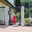 Jeune fille sur l'entrée à pavés, devant un portillon de jardin couleur anthracite assorti à la clôture à barres