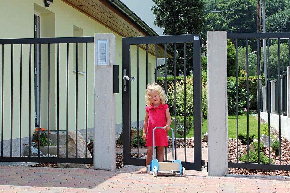 petite fille tenant une trottinette devant un portillon de jardin couleur anthracite doté de barres rondes simples