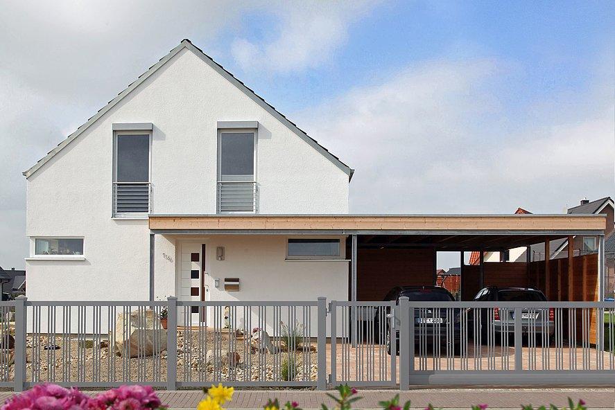 Clôture de jardin avec portillon de jardin et portail coulissant couleur grise, clôture à barres devant une maison unifamiliale moderne avec abri auto