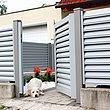 portillon de jardin à lamelles occultantes ouvert, avec un petit chien à l'entrée