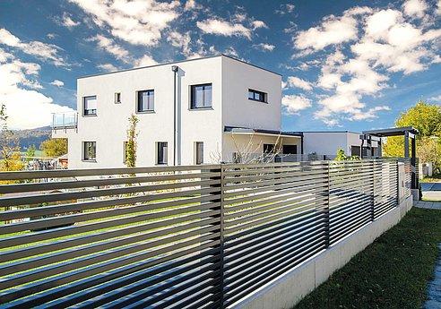 clôture de jardin moderne avec lattes transversales couleur anthracite devant une maison à architecture moderne