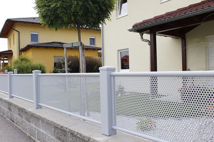 Vue rapprochée d'une clôture de jardin blanche occultante en tôle perforée dans un quartier résidentiel