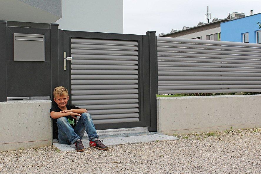 Jeune garçon adossé sur le portillon de jardin à lamelles grises en aluminium sur socle mural blanc