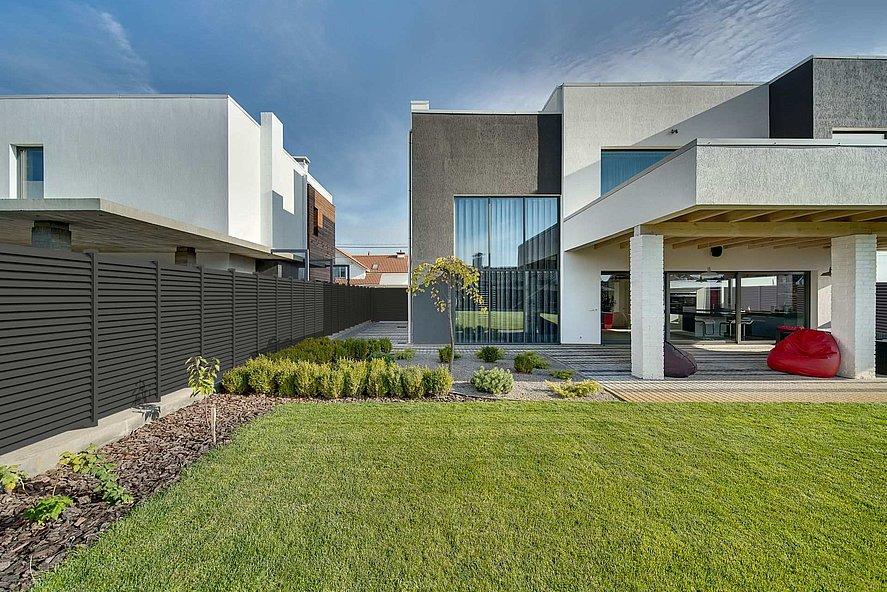 Vue depuis le jardin sur une villa moderne entourée par une clôture à lamelles moderne couleur gris foncé