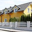 Clôture à palissade avec barres rondes et embouts coupe oignon couleur argent devant un habitat collectif
