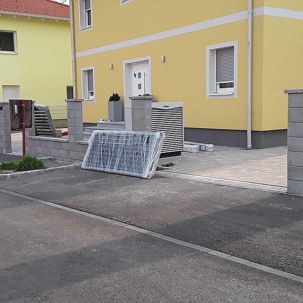 Montage d'une nouvelle clôture à lattes de couleur noire devant une maison jaune