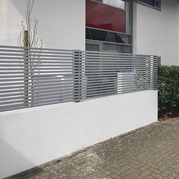 Clôture à lattes couleur argent, particulièrement moderne sur socle mural haut devant une maison moderne