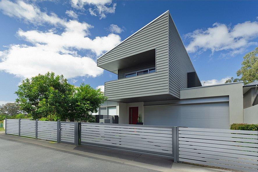 clôture moderne en aluminium avec portail coulissant électrique devant une maison design