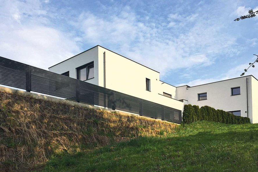 clôture à lattes moderne sur mur en pierres entourant une maison moderne à structure cubique