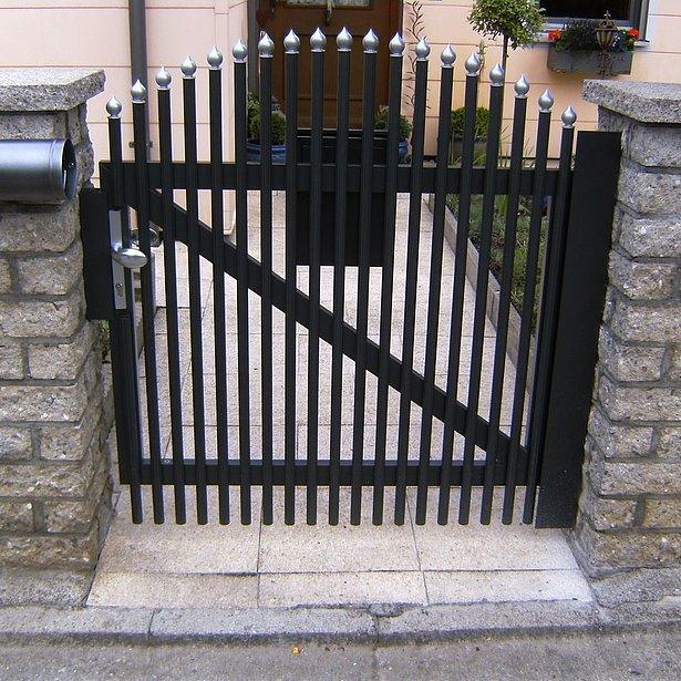 Portillon de jardin sur clôture à palissades couleur anthracite avec caches coupe oignon couleur argent entre deux socles en pierre maçonnés