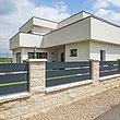 clôture moderne à lattes transversales larges couleur anthracite sur socles en brique devant une maison architecturale